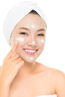 Vertical image of a girl moistening skin with cream